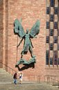 Michael and the devil coventry statue of st holding a spear over on wall of new cathedral west midlands Stock Images
