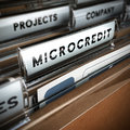 Microcredit folder with focus on a tab and the word blur effect concept of company projects funding Royalty Free Stock Photo