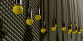 Microphones dangling on sound proof acoustic foam a front view of a row of yellow by cords at various heights a grey wall Stock Photos