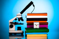 Microscope books and an alarm clock on the table student Royalty Free Stock Images