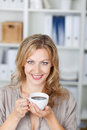 Mid adult businesswoman holding coffee cup in office closeup portrait of Royalty Free Stock Image