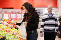 Mid adult woman buying fruit at supermarket women a Royalty Free Stock Image