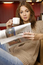 Mid adult woman drinking coffee and reading news Royalty Free Stock Image