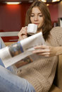 Mid adult woman drinking coffee and reading news Stock Photography