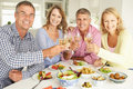 Mid age couples at home having a meal Royalty Free Stock Photo