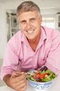 Mid age man enjoying salad Royalty Free Stock Photos