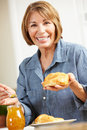 Mid age woman eating croissants Royalty Free Stock Photography