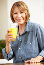 Mid age woman holding orange juice Royalty Free Stock Photo