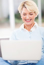 Mid age woman laptop cheerful using computer at home Royalty Free Stock Photo