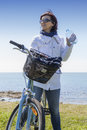 Mid aged healthy woman with water bottle on mountain bike Royalty Free Stock Photo