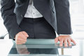 Mid section of businessman with clenched fist on office desk close up a well dressed the at Royalty Free Stock Images