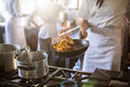 Mid section of chef cooking in kitchen stove Royalty Free Stock Photo