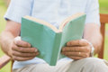 Mid section of a man reading a book at park Royalty Free Stock Photos
