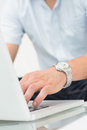 Mid section of a man using laptop on coffee table Royalty Free Stock Images