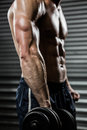 Mid section of shirtless man lifting heavy dumbbell Royalty Free Stock Photo