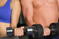 Mid section of a shirtless man and woman with dumbbells Stock Images