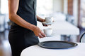 Mid section of waitress serving cup of coffee Royalty Free Stock Photo