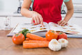 Mid section of a woman with recipe book and vegetables closeup in the kitchen at home Stock Image