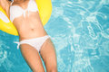 Mid section of a woman in white bikini floating on inflatable tube in swimming pool Royalty Free Stock Photo
