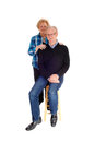Middle age couple in portrait image a senior standing isolated for white background the men sitting on a chair the wife standing Stock Photo