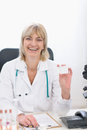 Middle age doctor woman showing business card Stock Photo