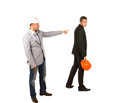 Middle age engineer pointing his co engineer in gray coat wearing black attire holding orange helmet captured on white background Stock Image