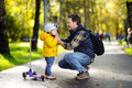 Middle age father helping his little son to put his helmet. Active toddler boy to ride a scooter. Royalty Free Stock Photo