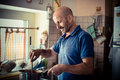 Middle age man cooking at home Royalty Free Stock Images