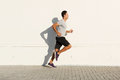 Middle age man running by white wall Royalty Free Stock Photo