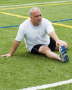 Middle age man stretching on sports field Stock Photos