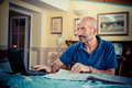 Middle age man using notebook at home Stock Images