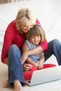 Middle age woman with young girl using laptop Royalty Free Stock Photography