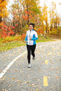 Middle aged asian woman running active in her s mature female jogging outdoor living healthy lifestyle beautiful autumn city park Stock Photography