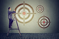 Middle aged business man on a ladder drawing a target on a wall Royalty Free Stock Photo