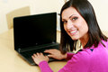 Middle aged cheerful woman using laptop and looking on the camera Royalty Free Stock Photo