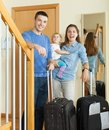 Middle aged couple with baby with luggage near door in home Royalty Free Stock Image