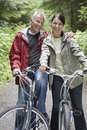 Middle aged couple with bikes in forest portrait of happy mature men and women Royalty Free Stock Photos