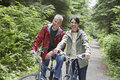 Middle aged couple with bikes in forest portrait of happy mature men and women on road Royalty Free Stock Photography