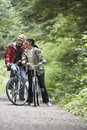 Middle aged couple with bikes on forest road cheerful mature men and women Stock Photography