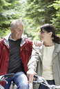 Middle aged couple with bikes in forest smiling mature men and women Stock Photo