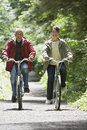 Middle aged couple biking on forest road full length of a mature men and women Stock Photos