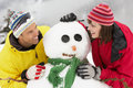 Middle Aged Couple Building Snowman On Ski Holiday Stock Photography