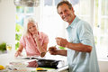 Middle aged couple cooking meal in kitchen together with husband smiling at camera whilst holding wooden spoon Royalty Free Stock Image