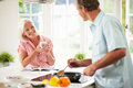 Middle aged couple cooking meal in kitchen together looking at each other smiling Stock Photo