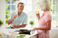 Middle aged couple cooking meal in kitchen together whilst holding a glass of white wine smiling at each other Stock Photography