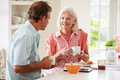 Middle aged couple enjoying breakfast at home together in kitchen looking each other chatting Stock Images