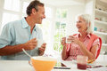 Middle aged couple enjoying breakfast at home together smiling each other whilst holding hot drink Stock Photo
