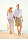 Middle aged couple enjoying walk on the beach happy romantic vacation retirement concept Stock Image