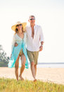 Middle aged couple enjoying walk on the beach happy romantic vacation retirement concept Royalty Free Stock Photo