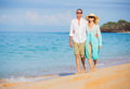 Middle aged couple enjoying walk on the beach happy romantic vacation retirement concept Royalty Free Stock Image